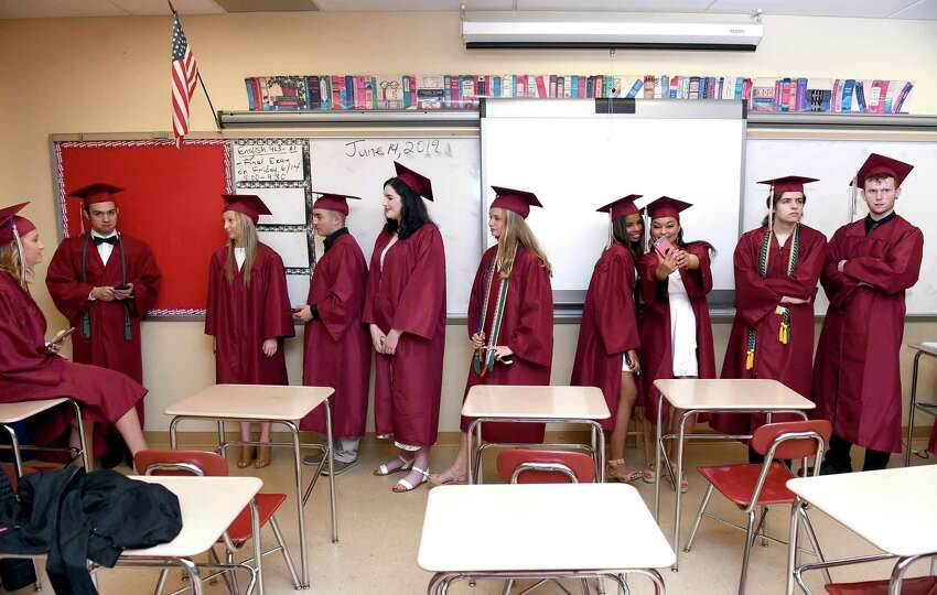 Graduates wait in a classroom to process into the gymnasium for the North Haven High School commencement on June 13, 2019.