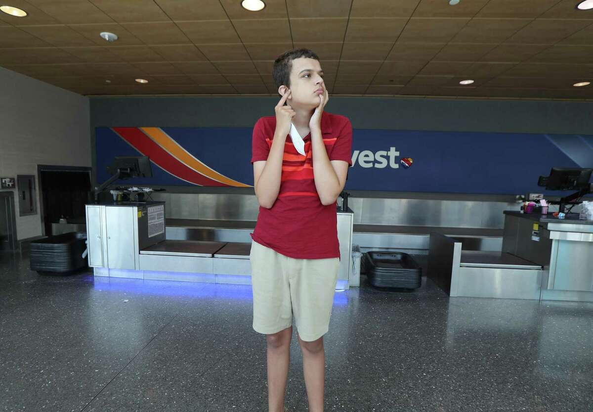"""Paul Perez, 13, moves away from the airport crowds Wednesday, June 12, 2019, in Houston. The Arc of the United States, Autism Society of Texas, Down Syndrome Association of Houston, Southwest Airlines and William P. Hobby Airport co-hosted Wings for All, an airport """"rehearsal"""" program to alleviate stress that individuals with intellectual and developmental disabilities and their families often experience when traveling by air."""
