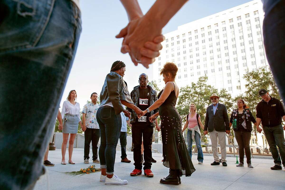 LOS ANGELES, CA - JUNE 12, 2019: Quintus Moore is in the center of 0 group of activists participate in a weekly protest outside the L.A. Hall of Justice, organized by LA Black Lives Matter, and is an activist for laws that would make it more difficult for law enforcement officers to resort to deadly force. Here they hold hands in prayer.