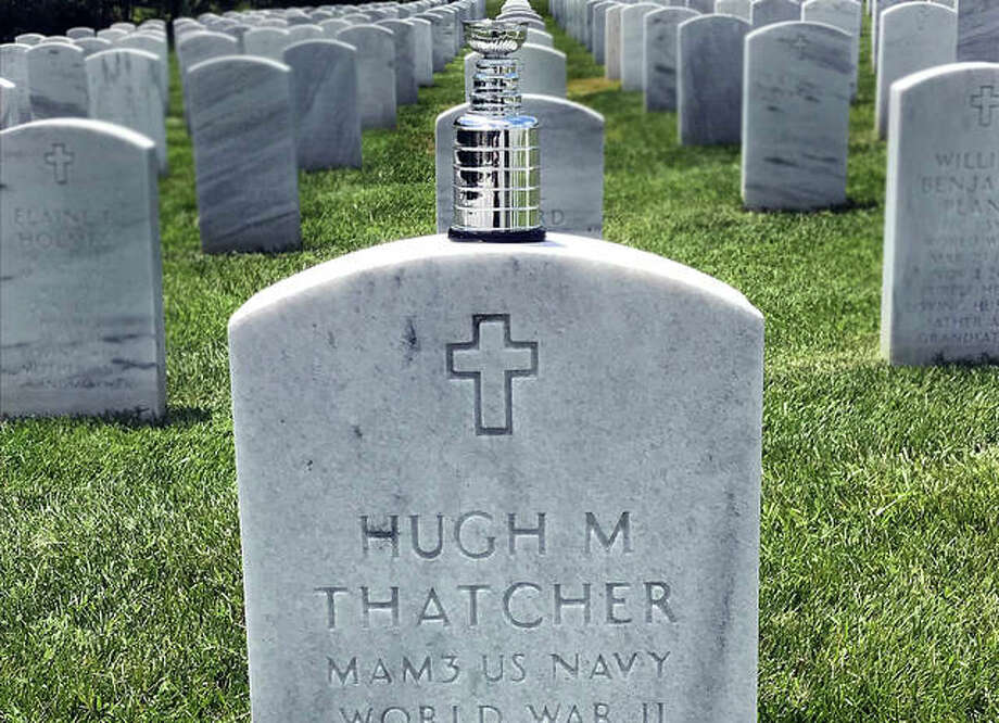 """A miniature Stanley Cup replica sits atop the gravestone of Hugh """"Hoot"""" Thatcher, the father of East Alton Ice Arena manager Larry Thatcher, who along with lifelong friend Dana Emerick have been devoted to the St. Louis Blues and the game of hockey since 1967. Thatcher and Emerick placed the miniature cup Thursday morning at Jefferson Barracks Cemetery."""