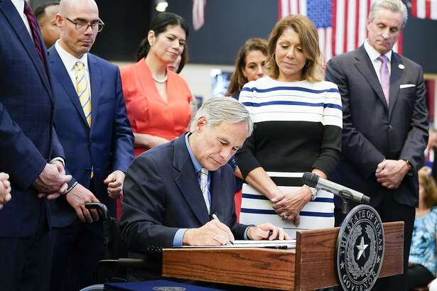 Texas Gov. Greg Abbott signs a Harvey-related measure at Gallery Furniture on Thursday, June 13, 2019 in Houston.