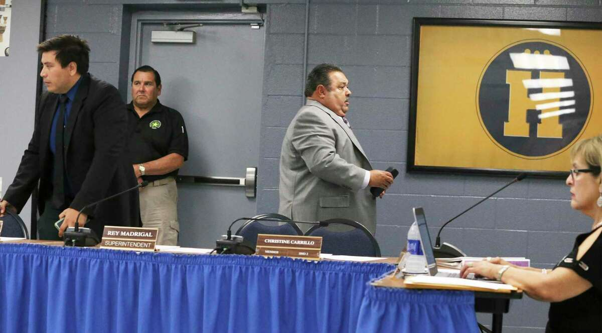 Harlandale ISD board president Ricardo Moreno, left, and Superintendent Rey Madrigal exit a meeting for executive session as the board met last June to discuss action on the Texas Education Agency's investigation report recommending a state takeover of the board. The board forced Madrigal out and on Friday learned they had averted the takeover but would operate under a state conservator.