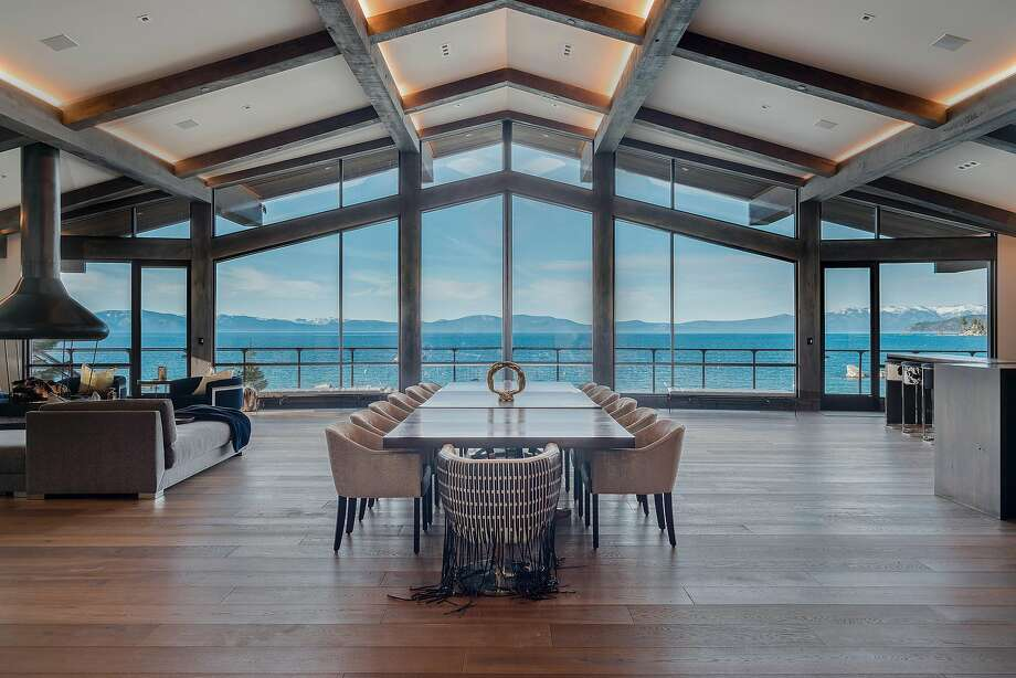 Hardwood flooring lines a great room that includes a floating fireplace and floor-to-ceiling windows framing views of Lake Tahoe. Photo: (c)William Rittenhouse William C. Rittenhouse