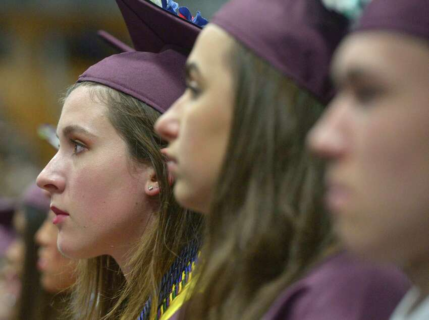 Madelyn Montague Wachniuk, left, listens to a speaker during the Bethel High School Class of 2019 Commencement Ceremony, Thursday June 13, 2019, at the O'Neill Center, Western Connecticut State University, Danbury, Conn. Eve Vucinaj is center.