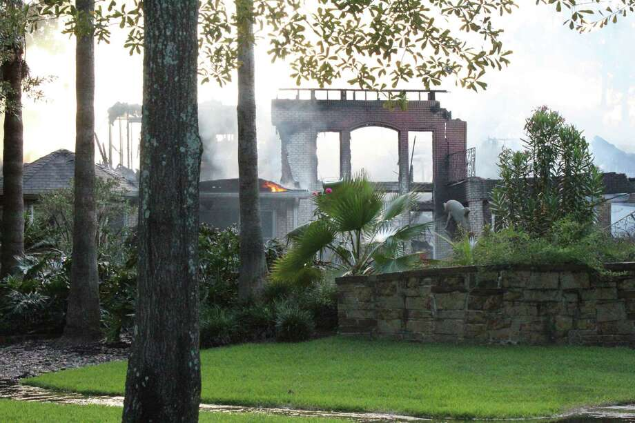 Two people were injured and a more than 7,000 square foot mansion home in The Woodlands was destroyed Thursday night after a fire tore through the palatial French-style home.Battalion Chief Jason Washington of The Woodlands Fire Department said the fire was reported at about 5:30 p.m. Thursday by neighbors. More than 60 firefighters and numerous medical personnel responded to the home located at 46 Palmer Crest in the Village of Cochran's Crossing, adjacent to the third hole of The Woodlands Country Club Palmer golf course. Photo: Photos By Jeff Forward/The Villager