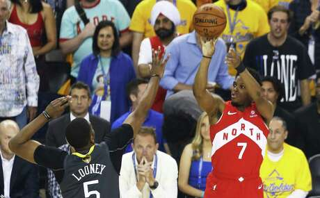 OAKLAND, CALIFORNIA - JUNE 13: Kyle Lowry #7 of the Toronto Raptors scores a three point basket past Kevon Looney #5 of the Golden State Warriors in the first half during Game Six of the 2019 NBA Finals at ORACLE Arena on June 13, 2019 in Oakland, California. NOTE TO USER: User expressly acknowledges and agrees that, by downloading and or using this photograph, User is consenting to the terms and conditions of the Getty Images License Agreement. (Photo by Lachlan Cunningham/Getty Images)