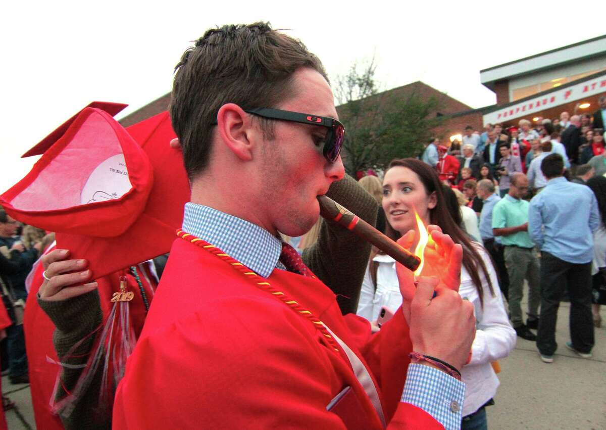 Graduate Dylan Post lights up a cigar at the conclusion of Pomperaug High School's Commencement Ceremony in Southbury, Conn., on Thursday June 13, 2019.