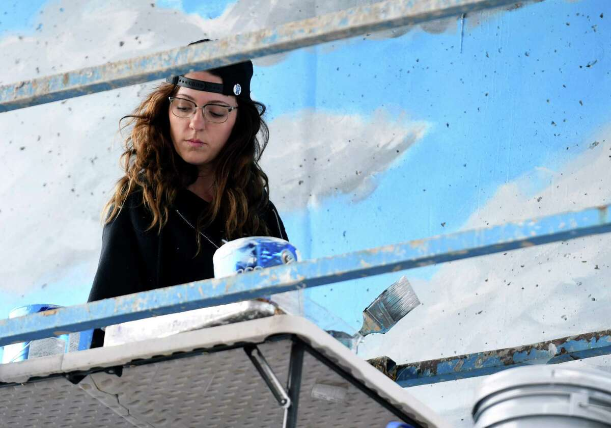 Vanessa Mastronardi, Canadian artist and University of Albany graduate, works on her mural beneath the I-787 off-ramp to Clinton Ave. on Thursday, June 13, 2019, at the Albany Parking Authority?s Quackenbush Lot in Albany, N.Y. Mastronardi's mural is part of Capital Walls, a collaborative effort between Albany Center Gallery, the Albany Barn and the Albany Parking Authority to inspire the community with uplifting, educational and thought-provoking public works of art. (Catherine Rafferty/Times Union)