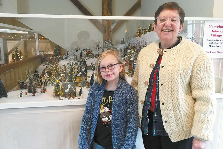 Moira Craw is joined by her granddaughter, Siri Quarfordt, 9, at the Christmas village's new home at the Wilton Historical Society. — Allison Sanders photo