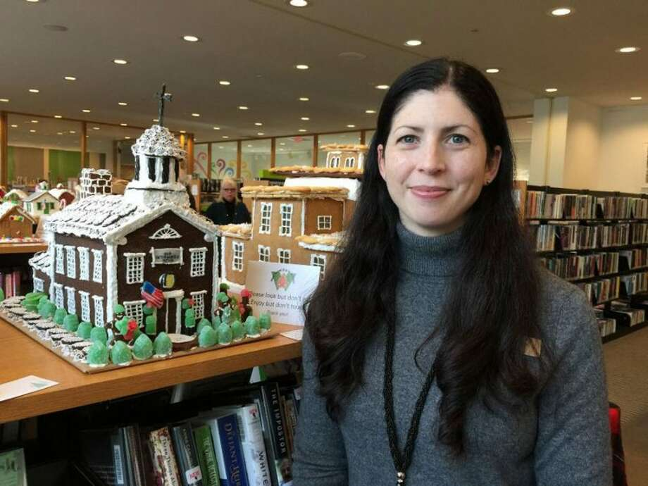 "Melissa Baker, media and digital services librarian for Wilton Library, enjoys the entries in the 'How Sweet It Is In Wilton,"" gingerbread house contest. — Patricia Gay photo"