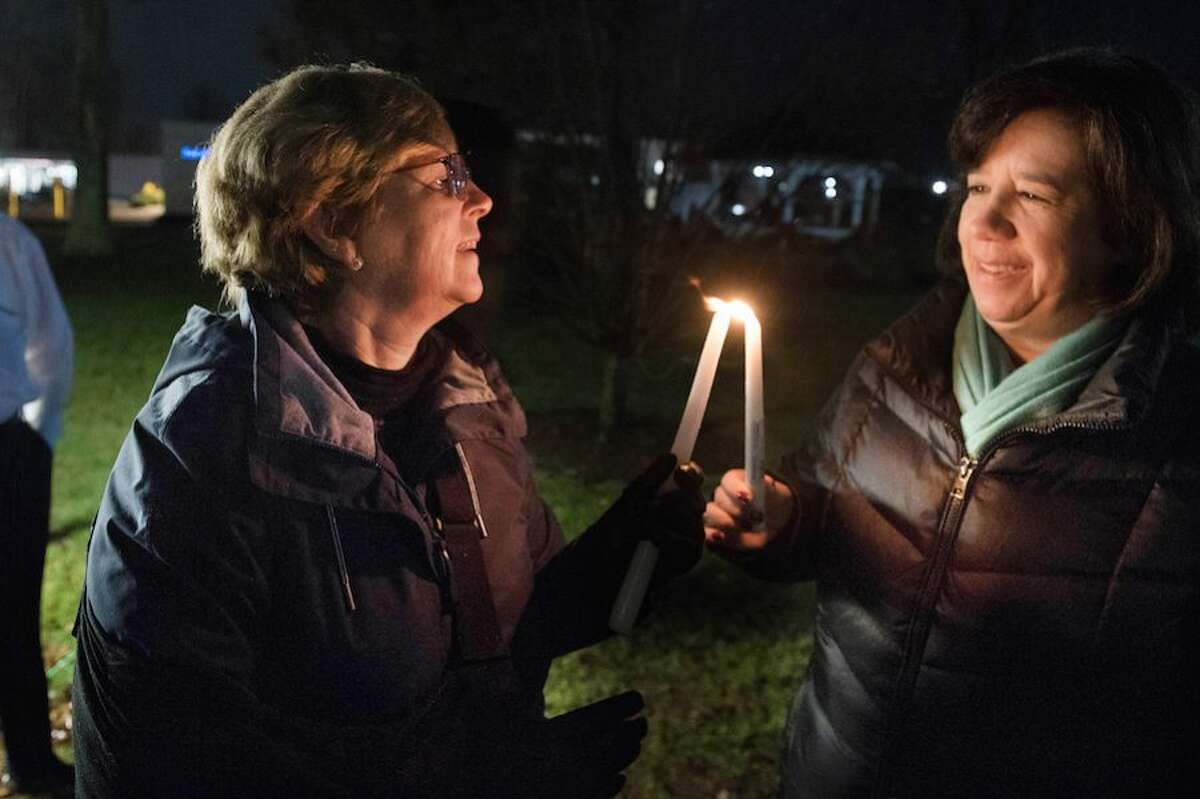 First Selectwoman Lynn Vanderslice, left, and Selectwoman Lori Bufano each hold a shamash which is a candle to help light the menorah.