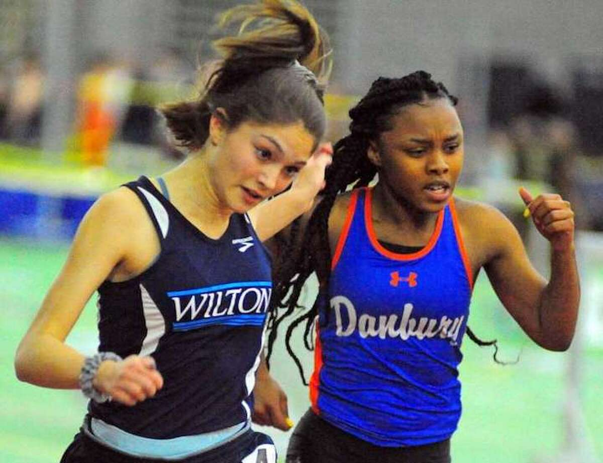 Wilton's Shelby Dejana and Danbury's Shanell Stewart compete in the 55-meter dash during the FCIAC girls indoor track championship meet. - Christian Abraham/Hearst Connecticut Media