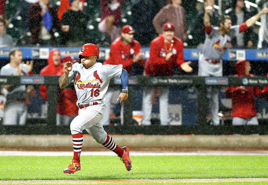 Cardinals players react from the dugout as' Kolten Wong hustles home on Harrison Bader's double in the ninth inning Thursday night against the New York Mets in New York. Photo: AP Photo