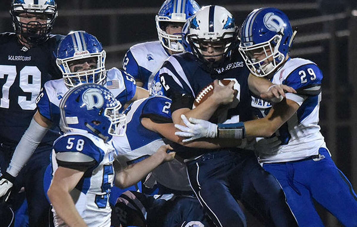 A swarm of Darien defenders puts the brakes on Wilton's Kyle Phillips during the Wave's 34-13 win on Friday night. - Dave Stewart photo