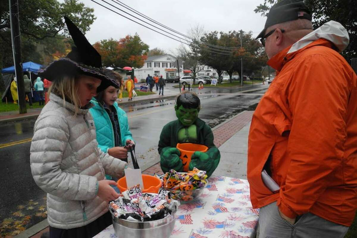 A trio of trick-or-treaters, two witches and the Incredible Hulk, stop by the American Legion table manned by Tom Moore.