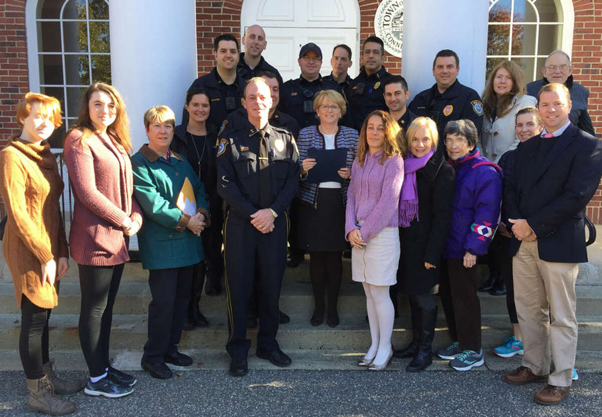 Those attending a reading of a domestic violence awareness proclamation, front row, from left, Macaire McNamara, Lauren McNamara, Kris Fager, Police Chief John Lynch, Kim Zemo, Margaret Creeth, Barbara Holdridge, and Dr. Kevin Smith. Second row, Sarah Heath, Sgt. Anthony Cocco, First Selectwoman Lynne Vanderslice, Captain Rob Cipolla, Maureen McGrath. Third row, Officer Rob Smaldone, Officer Jon Patry, Officer Vincent Penna, Lt. David Hartman, Jennifer McNamara, and Jerry Holdridge. Back row, Officer Frank Razzaia and Officer Joseph Caloross