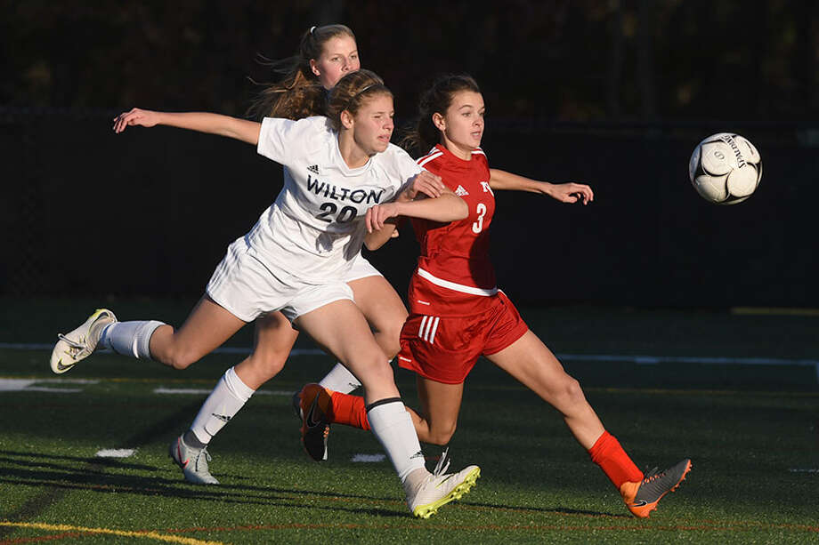 New Canaan's Dillyn Patten and Wilton's Maddie Wecker pursue the ball during the FCIAC girls soccer quarterfinals Thursday at Dunning Field. — Dave Stewart photo