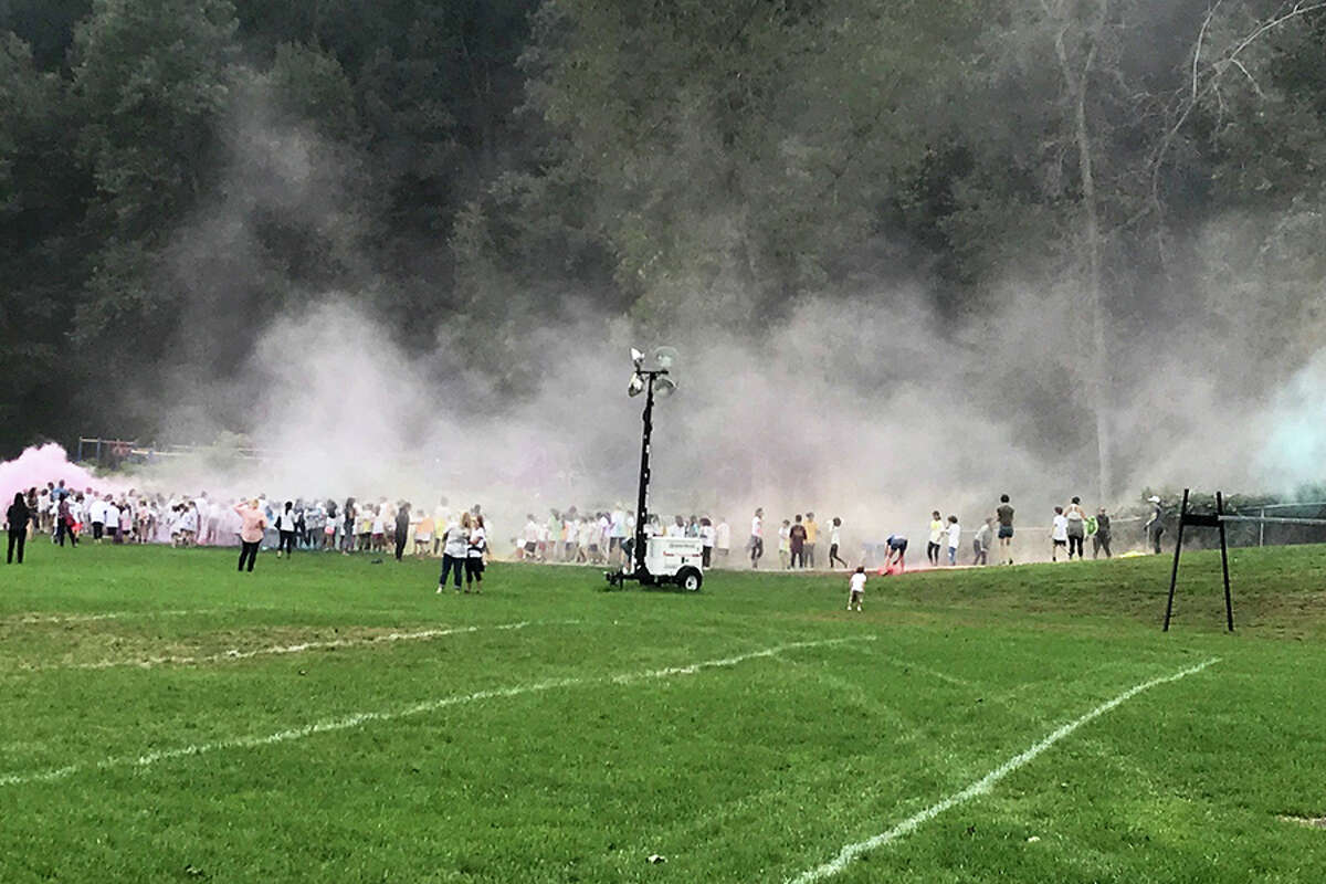 Students get doused with color powder at the end if the Cider Mill Walkathon. - Contributed photo