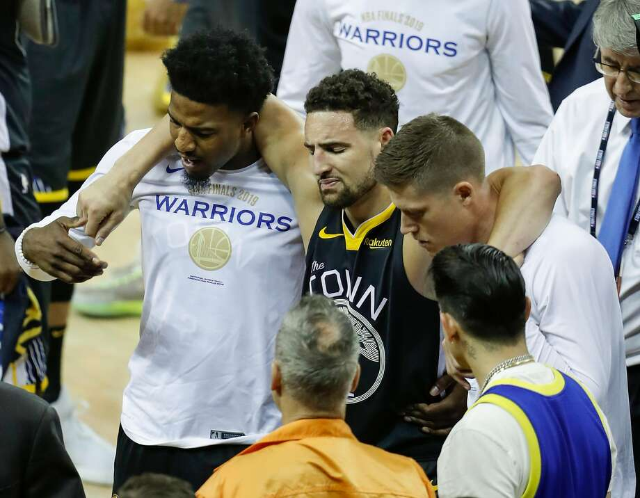 Golden State Warriors' Klay Thompson is helped off the court by Jordan Bell and Jonas Jerebko in the third quarter during game 6 of the NBA Finals between the Golden State Warriors and the Toronto Raptors at Oracle Arena on Thursday, June 13, 2019 in Oakland, Calif. Photo: Scott Strazzante, The Chronicle