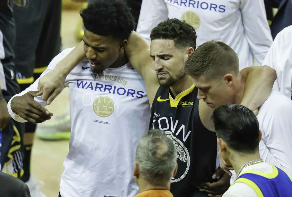 Golden State Warriors' Klay Thompson is helped off the court by Jordan Bell and Jonas Jerebko in the third quarter during game 6 of the NBA Finals between the Golden State Warriors and the Toronto Raptors at Oracle Arena on Thursday, June 13, 2019 in Oakland, Calif.