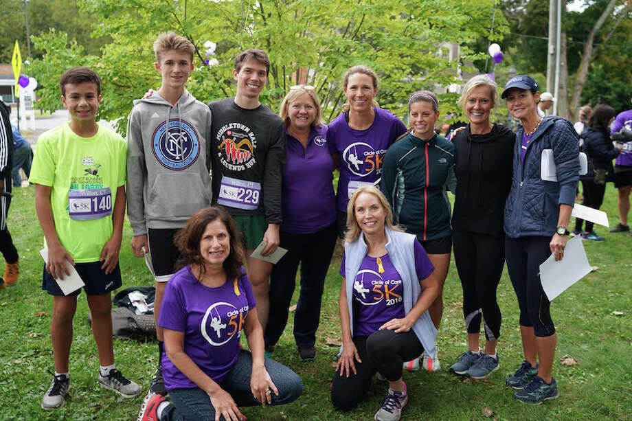 Circle of Care co-founders Dawn Ladenheim and Liz Salguero, kneeling, and executive director Gina Longo, center, are joined by the top finishers in Sunday's 5K from left: Matthew Ferrante,Thomas Arnold, Piotr Kostyk, Beth Cristini, Samantha Desimone, and Angela Nolan. At right is volunteer Kacky Theoharides. — Jeff Salguero photos