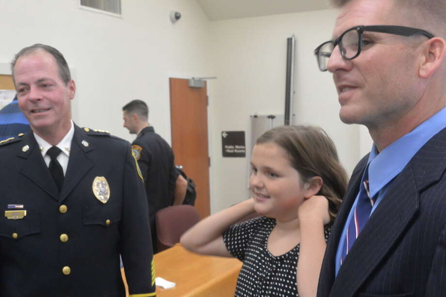 Newly sworn-in Officer Graham O'Gorman, right, smiles with his daughter Emma and Chief John Lynch. — Tony Spinelli photo