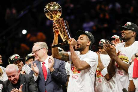 Toronto Raptors' Kawhi Leonard hoists the Larry O'Brien NBA Championship Trophy after their 114 to 110 victory over the Warriors in game 6 of the NBA Finals at Oracle Arena on Thursday, June 13, 2019 in Oakland, Calif.