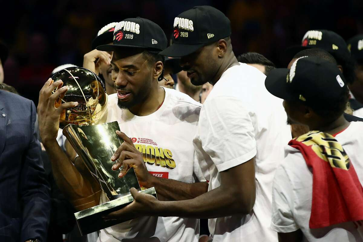 Kawhi Leonard #2 of the Toronto Raptors celebrates with the Larry O'Brien Championship Trophy after his team defeated the Golden State Warriors to win Game Six of the 2019 NBA Finals at ORACLE Arena on June 13, 2019 in Oakland, California.