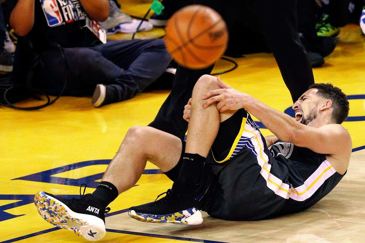 Golden State Warriors' Klay Thompson falls to the floor in pain in the third quarter during game 6 of the NBA Finals between the Golden State Warriors and the Toronto Raptors at Oracle Arena on Thursday, June 13, 2019 in Oakland, Calif.