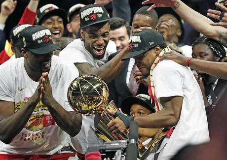 Toronto Raptors' Kyle Lowry holds the Larry O'Brien trophy as Kawhi Leonard exults after Raptors' 114-110 win over Golden State Warriors in Game 6 of NBA Finals at Oracle Arena in Oakland, Calif., on Thursday, June 13, 2019.