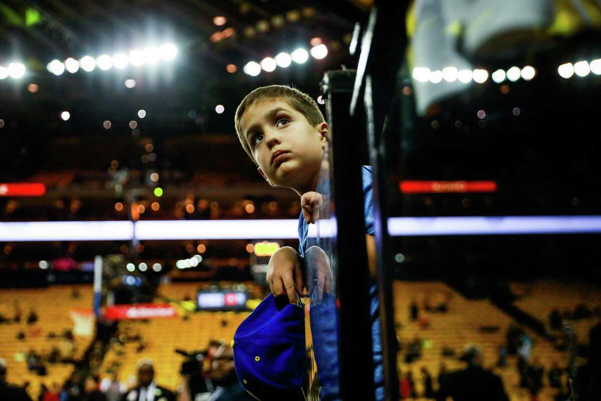 Warriors fan Mark Corso, 7, waits for players to come out to sign autographs at Oracle Arena.