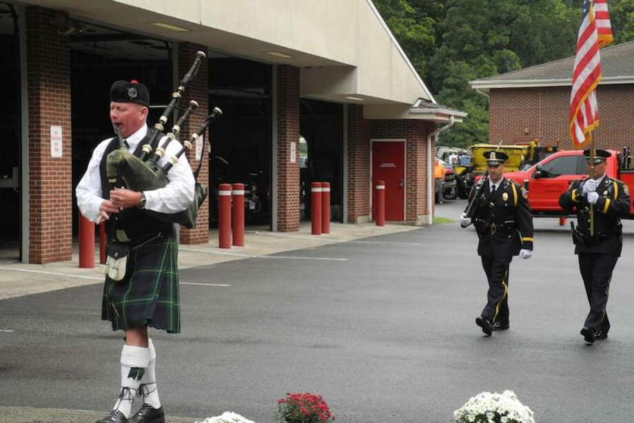 Bagpiper Drew Kennedy leads the procession.