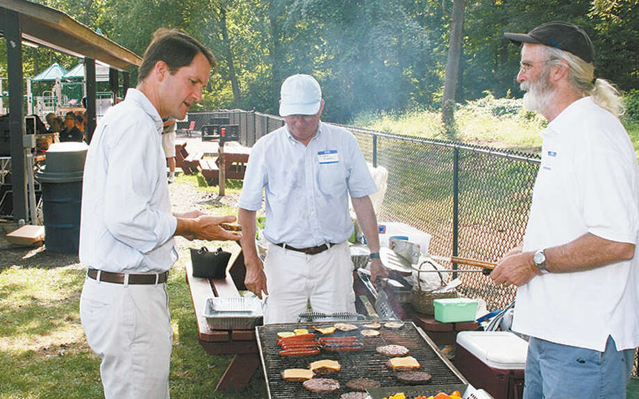 Congressman Jim Himes, left, gets a burger at last year's barbecue. Manning the grill are Richard Creeth, center, and Paul Burnham.