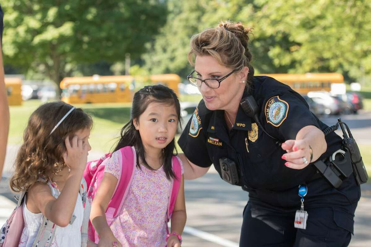 School Resource Officer Diane MacLean points the way for two students.