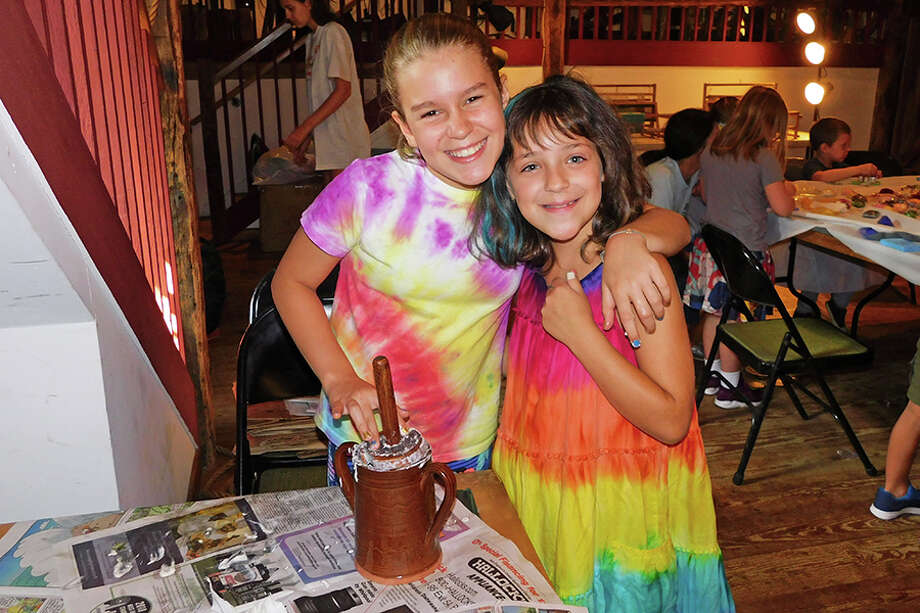 Caitlyn Lentner, 10, left, and Siena Criscuolo, 8, churn butter at Wilton Historical Society's Colonial Boot Camp on Aug. 27. / NikonCoolpix