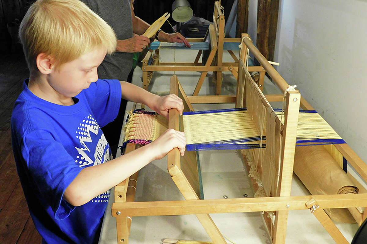 Aiden Cocoa, 8, uses a table loom to weave at Colonial Boot Camp.