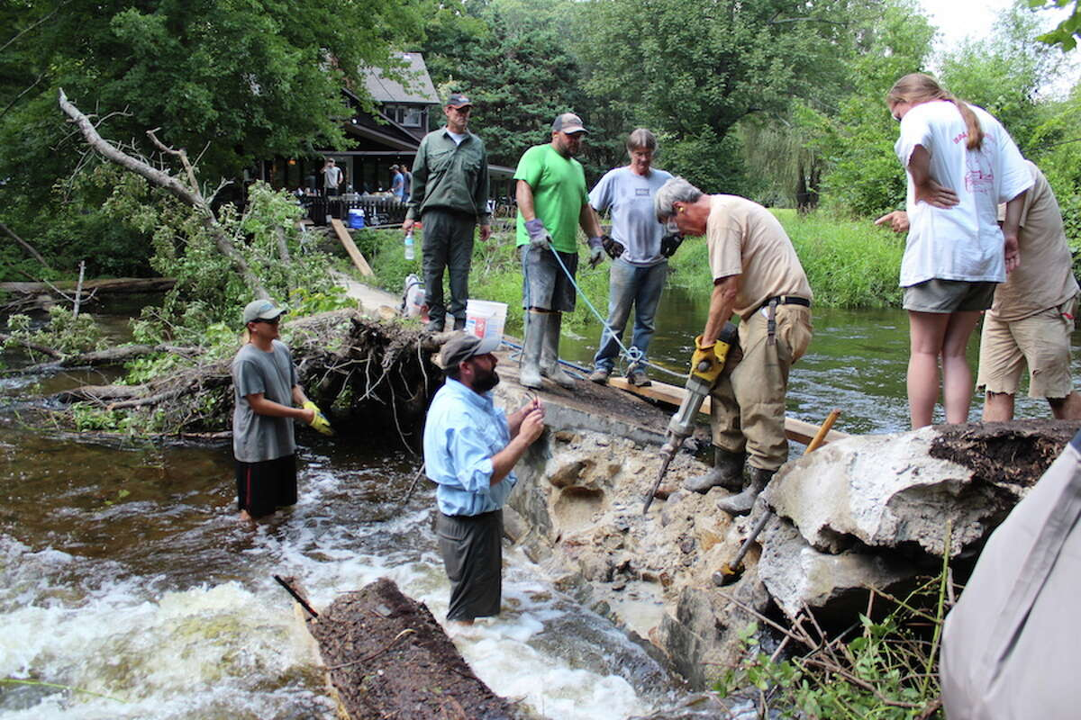 Gerrald Berrafati and Jeff Yates (in water) and Bill Carpenter of Ridgefield (on dam) of the Mianus Chapter of Trout Unlimited work with members of the Connecticut Department of Energy and Environmental Protection's Diadromous Fish Restoration Project to remove the Cannondale Dam on Aug. 19, 2018. In green holding a safety cord is Fisheries Biologist Dave Ellis, to his left is Seasonal Resource Assistant Kirk McPherson, and Fisheries Biologist Bruce Williams is operating the jackhammer. - John Kovach photo