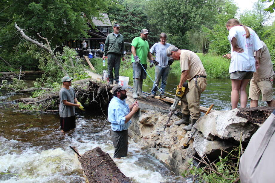 Gerrald Berrafati and Jeff Yates (in water) and Bill Carpenter of Ridgefield (on dam) of the Mianus Chapter of Trout Unlimited work with members of the Connecticut Department of Energy and Environmental Protection's Diadromous Fish Restoration Project to remove the Cannondale Dam on Aug. 19, 2018. In green holding a safety cord is Fisheries Biologist Dave Ellis, to his left is Seasonal Resource Assistant Kirk McPherson, and Fisheries Biologist Bruce Williams is operating the jackhammer. — John Kovach photo