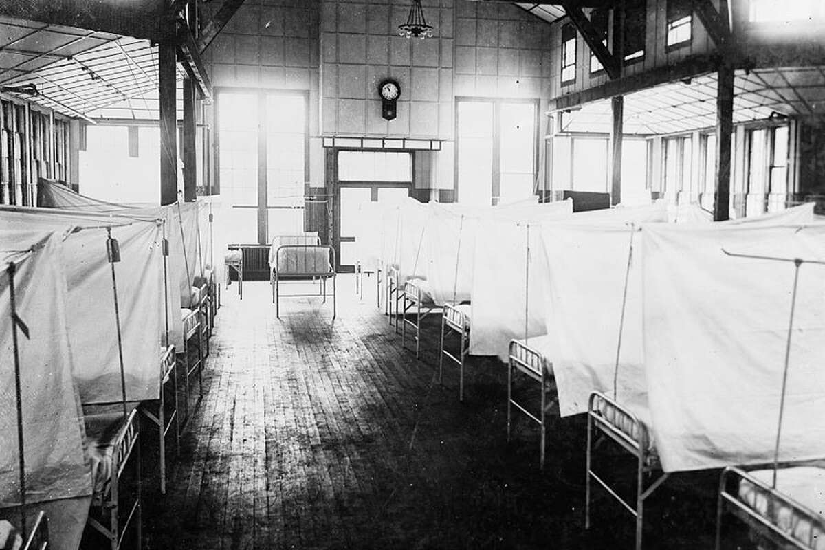 Beds isolated by curtains inside a New Haven hospital during the 1918 influenza pandemic. - Library of Congress photo