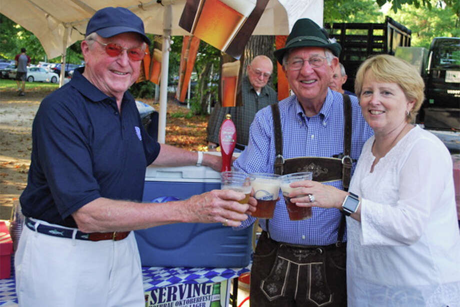 Three Wilton first selectmen — Bill Brennan, left, Paul Hannah, and Lynne Vanderslice — raise a glass of German beer at the Kiwanis Club's Oktoberfest last year. — Contributed photo