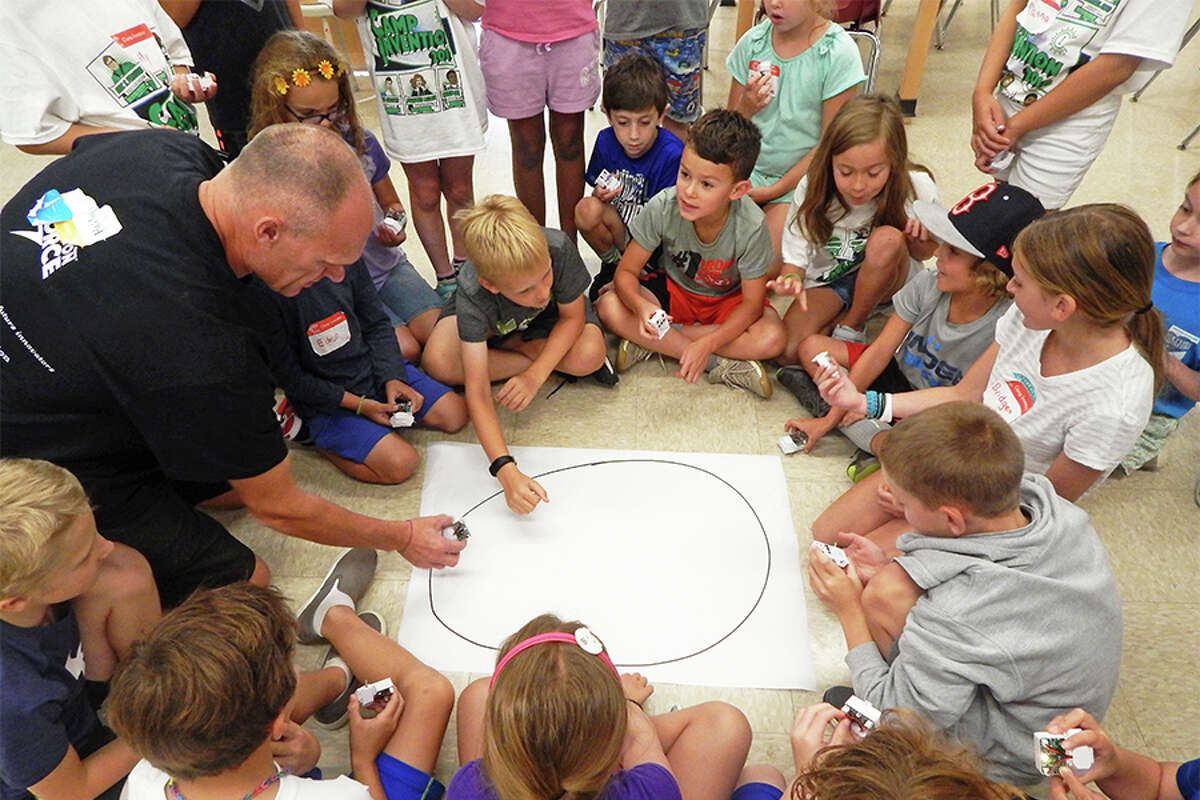 Instructor Jason Greasley explains and shows campers how an Optibot follows marker-drawn lines during Wilton's second Camp Invention week.