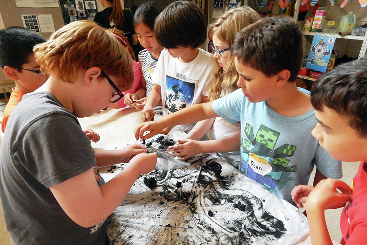 Campers play with slime as part of Camp Invention's Stick To It module.