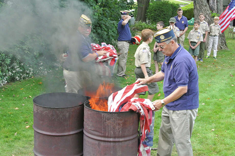 American Legion Post 86 Commander Don Hazzard places a flag in the flames as Adjutant Tom Moore receives another flag for retirement in 2017. — Jeannette Ross photo
