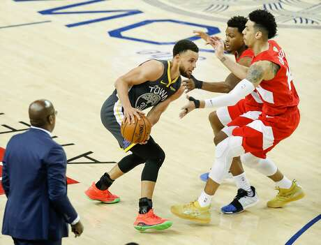 Golden State Warriors' Stephen Curry is double-teamed by Toronto Raptors' Kyle Lowry and Danny Green in the fourth quarter during game 6 of the NBA Finals between the Golden State Warriors and the Toronto Raptors at Oracle Arena on Thursday, June 13, 2019 in Oakland, Calif.