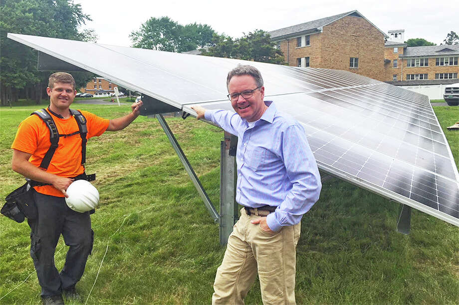 Corey Koenig, co-owner of KMK Solar Structures, joins Mark Robbins, founder and president of MHR Development, at the ground-mounted solar array at the School Sisters of Notre Dame campus on Belden Hill road. KMK Solar Structures installed the solar panels. — Contributed photo