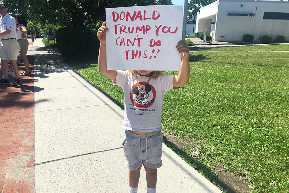 A child at the rally holds a sign reading, 'Donald Trump, you can't do this!!'