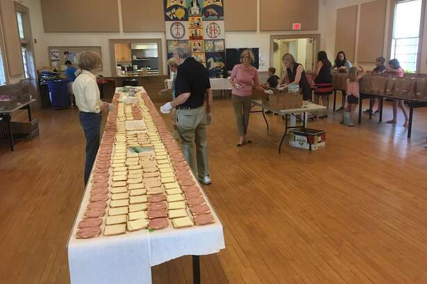 Volunteers at Wilton Congregational Church form an assembly line to make sandwiches for children in need.