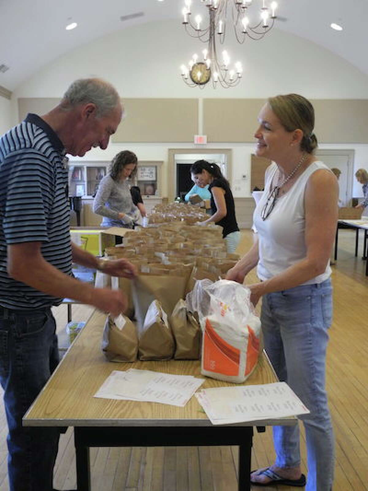 Giff Broderick and Kathy Scheller pack some of the 230 bag lunches with church volunteers. - Jeannette Ross photo