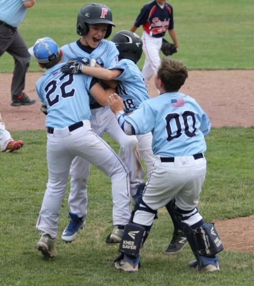 Tanner Schmauch is mobbed by his teammates after his RBI double in the bottom of the sixth gave the Wilton 11U baseball team a walk-off 10-9 win over Stamford North on Sunday. — Vin Forgione photo