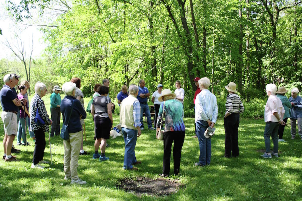 Members of Stay at Home in Wilton listen to land trust executive director Donna Merrill during a walk through Schenck's Island. - Debbie Louis photo